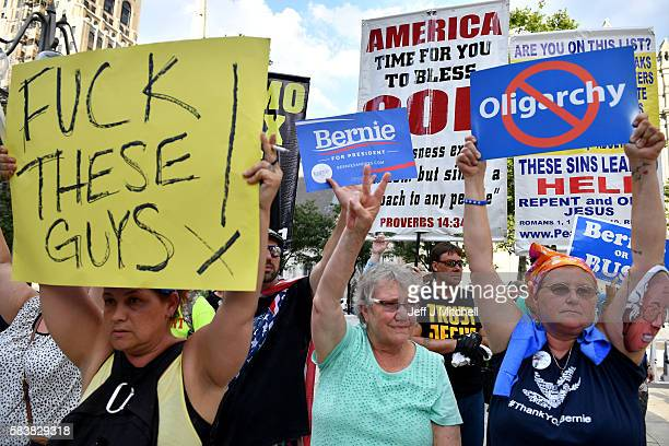 Bernie Sanders supporters hold banners in front of a in front of a religious group as they gathered near City Hall on day three of the Democratic...