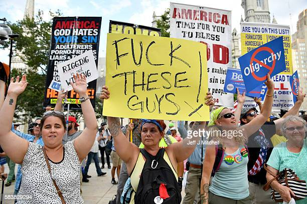 Bernie Sanders supporters hold banners in front of a religious group as they gathered near City Hall on day three of the Democratic National...