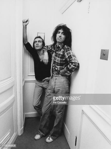 Bernie Taupin British songwriter standing beside US rock singer Alice Cooper circa 1975 Copper leans against a wall with his arm on Taupin's shoulder