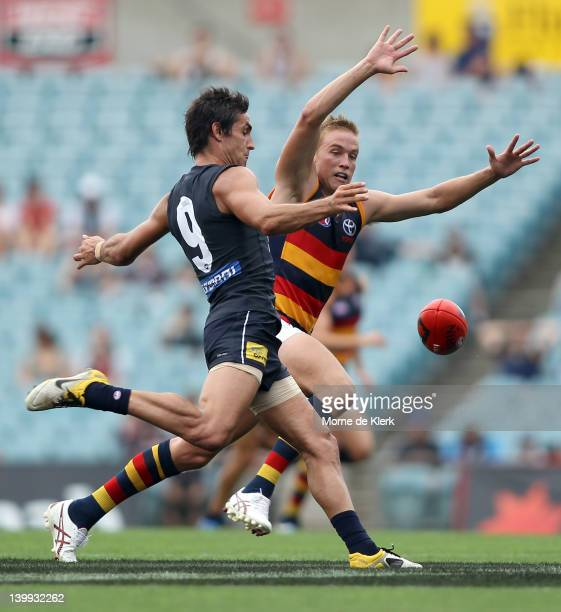 Bernie Vince of the Crows tries to smother a kick by Kane Lucas of the Blues during the round one NAB Cup AFL match between the Adelaide Crows and...