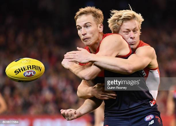 Bernie Vince of the Demons handballs whilst being tackled by Isacc Heeney of the Swans during the round 15 AFL match between the Melbourne Demons and...