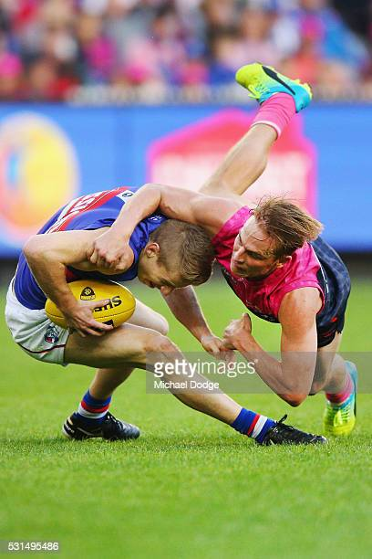 Bernie Vince of the Demons tackles Lachie Hunter of the Bulldogs during the round eight AFL match between the Melbourne Demons and the Western...