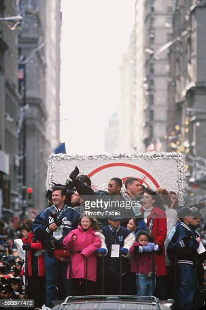 Bernie Williams and his family wave to fans lining the parade route from a Yankees float in celebration of the Yankees winning the World Series