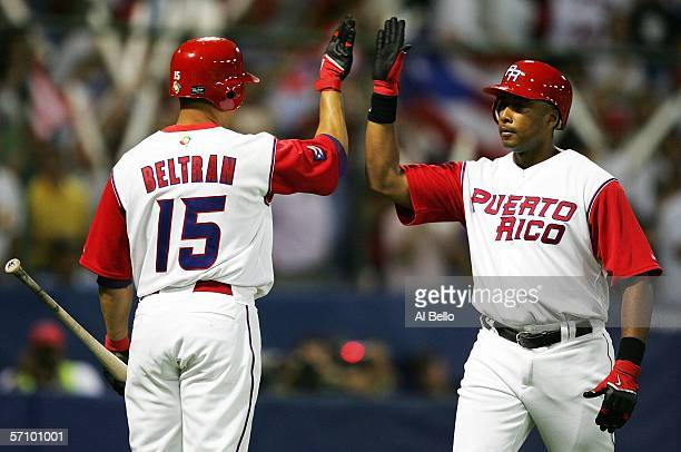 Bernie Williams of Puerto Rico celebrates with Carlos Beltran after hitting a home run against Cuba during Round 2 of the World Baseball Classic on...