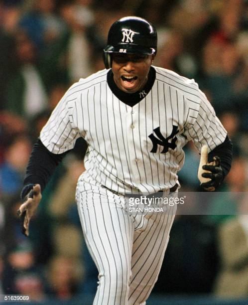 Bernie Williams of the New York Yankees celebrates after hitting a grand slam home run off pitcher Rick Helling of the Texas Rangers in fifth inning...