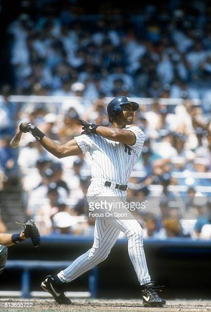 Bernie Williams of the New York Yankees swings and watches the flight of his ball during a Major League Baseball game circa 1996 at Yankee Stadium in...