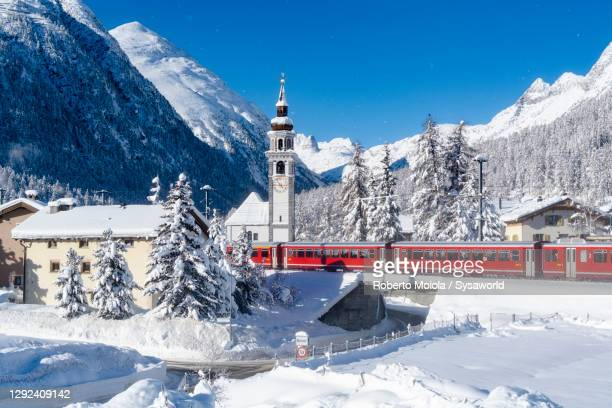 bernina express train along the snow capped village, switzerland - switzerland stock pictures, royalty-free photos & images