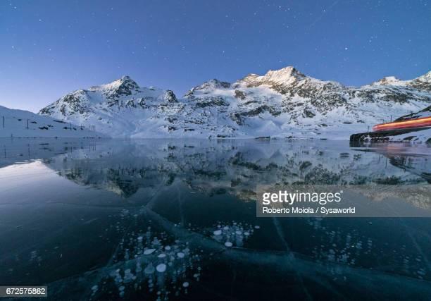 Bernina Express train at the frozen Lake Bianco Switzerland