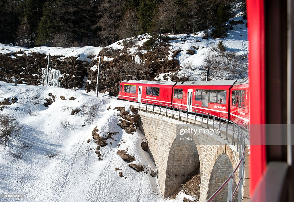Bernina red train climbing in the snow, view from window : Stock Photo