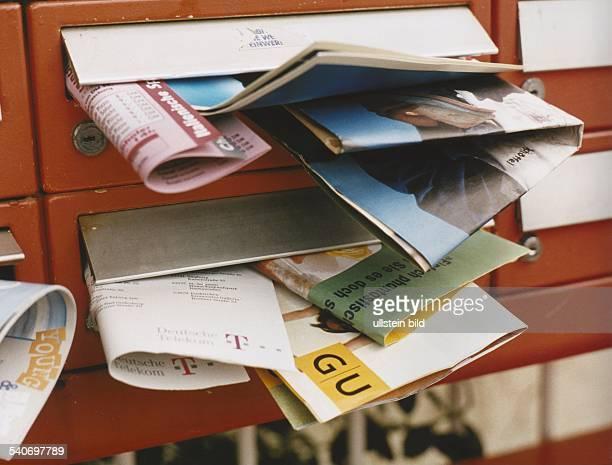 Überquellende Hausbriefkästen Prospekte verschiedener Firmen hängen aus den Schlitzen mehrerer Briefkästen