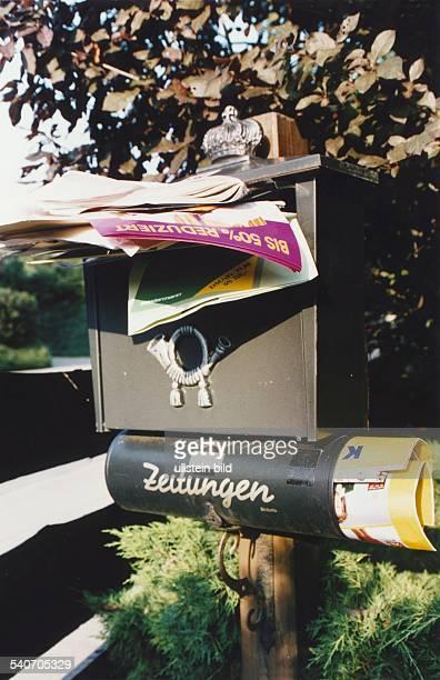 Überquellender Briefkasten vollgestopft mit Werbeprospekten und Zeitschriften
