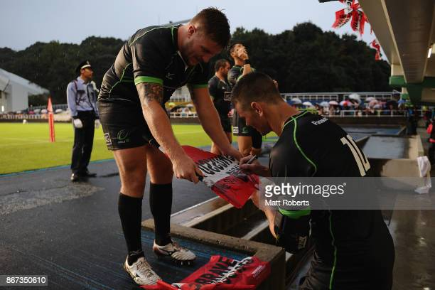 Berrick Barnes of World XV signs autographs with Facundo Gigena of World XV after the international match between Japan XV and World XV at Level Five...