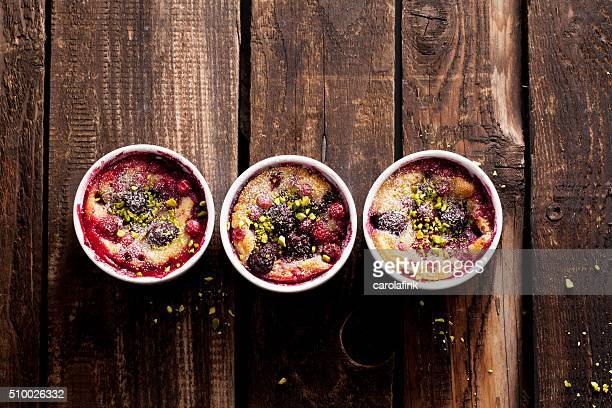 berries soufflé on wooden board served as dessert - carolafink stock photos and pictures