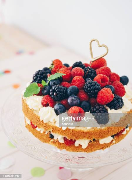 berry cake with heart shaped sparkler and confetti - sponge cake stock pictures, royalty-free photos & images