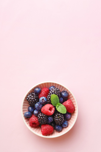 Berry (raspberry, blueberry, blackberry) fruits bowl on a pastel background. Top view. Copy space 931396066