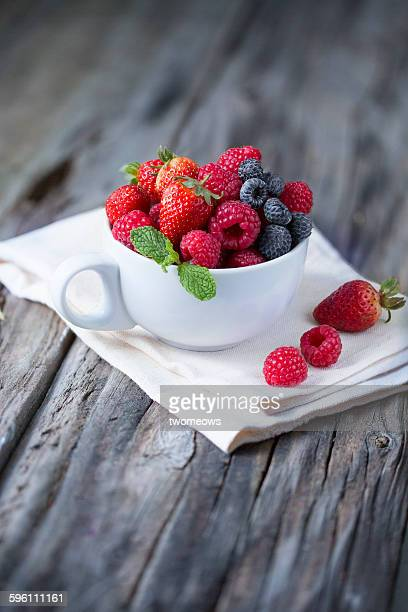 berry fruits family in cup on rustic wooden table - mint plant family fotografías e imágenes de stock