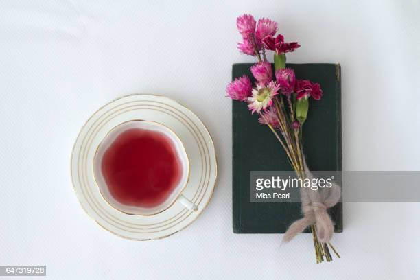 Berry tea with wild flowers and old book