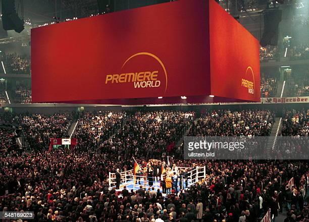 Blick über die Zuschauer auf den beleuchteten Boxring bei der Profiboxveranstaltung in der PreussagArena in Hannover über dem Ring hängen die roten...