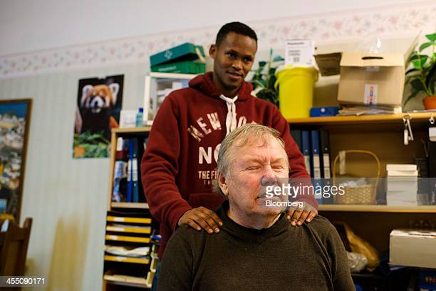 Bert Karlsson a Swedish music industry mogul receives a shoulder massage from a resident refugee at the Stora Ekeberg asylum center in Skara Sweden...