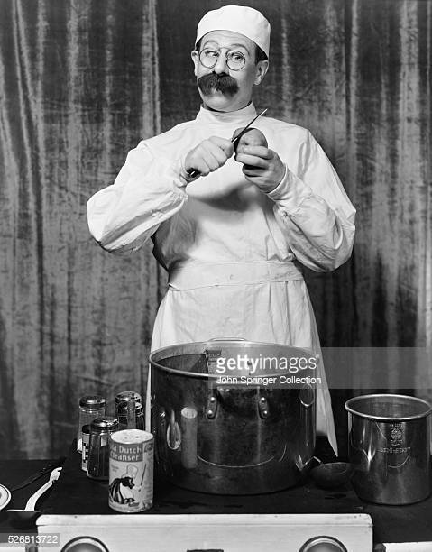 Bert Lahr dressed as a comical cook prepares a meal during a performance of George White's Scandals at the New Amsterdam Theatre