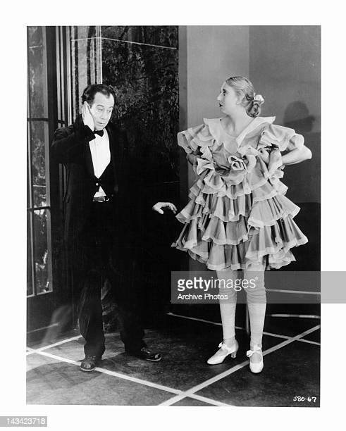 Bert Lahr with hand at his cheek as Charlotte Greenwood stands by in stare in a scene from the film 'Flying High' 1931