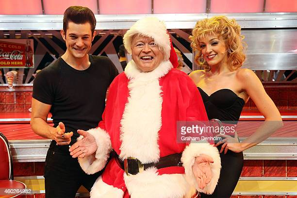 Bert Newton poses dressed as Santa Claus with Rob Mills as Danny and Gretel Scarlett as Sandy at the 'Grease' musical at The Regent Theatre on...
