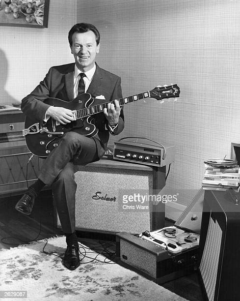 Bert Weedon the English guitarist popular in Britain during the 50's at his home in Wembley playing the guitar surrounded by audio equipment of the...