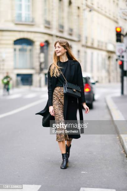 Bertille Canat wears a black wool long coat, a black pullover, a black quilted Chanel bag, a brown and black zebra pattern printed skirt, black...