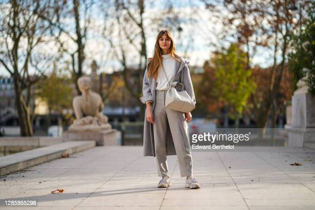 Bertille Canat wears a white turtleneck top from American Vintage, a gray long oversized wool coat from American Vintage, a white large leather bag...