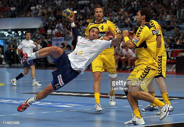 Bertrand Gille of Hamburg is challenged by Michael Mueller of Rhein Neckar during the EHF Final Four 3rd place match between Rhein Neckar Loewen and...