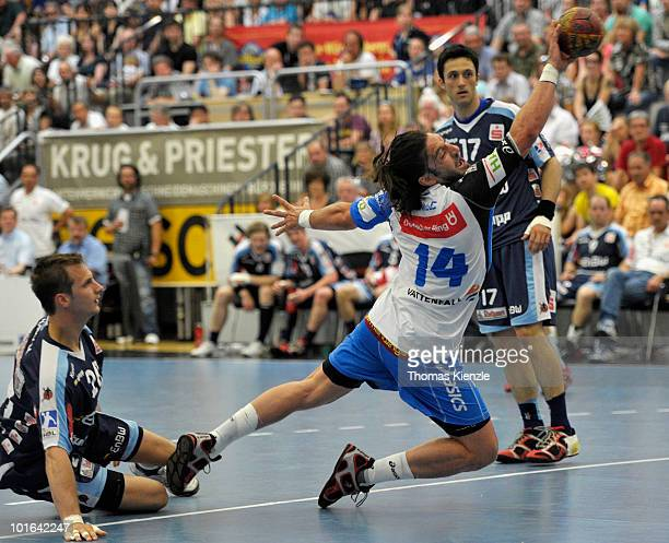 Bertrand Gille of Hamburg shoots at goal while Vladimir Temelkow and Markus Wagesreiter of Balingen look on during the Toyota HBL handball match...