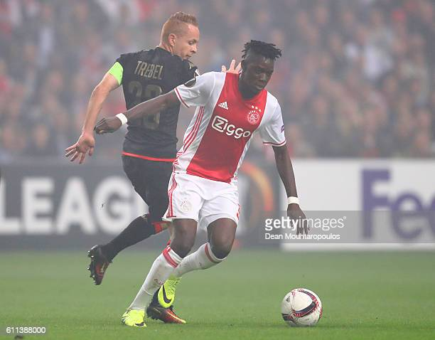 Bertrand Traore of Ajax is challenged by Adrien Trebel of Standard Liege during the UEFA Europa League group G match between AFC Ajax and R Standard...