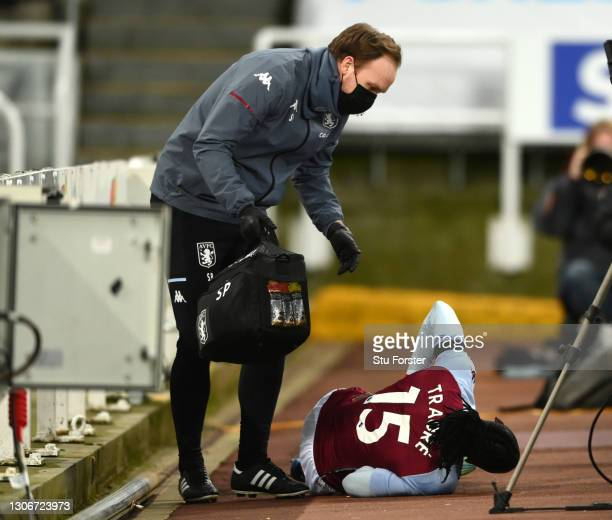 Bertrand Traore of Aston Villa receives medical attention after falling over the advertising boards during the Premier League match between Newcastle...
