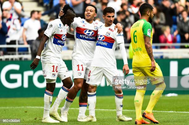 Bertrand Traore of Lyon celebrates after scoring a goal with Memphis Depay and Houssem Aouar during the Ligue 1 match between Olympique Lyonnais and...