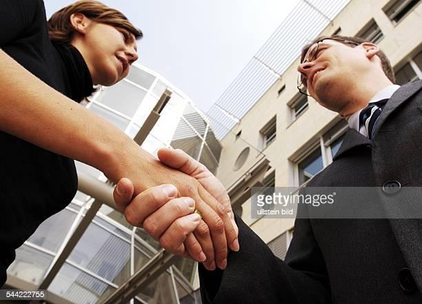Berufliche Kommunikation: Junge Frau begruesst ihren Kollegen oder Geschaeftspartner mit Handschlag. ,