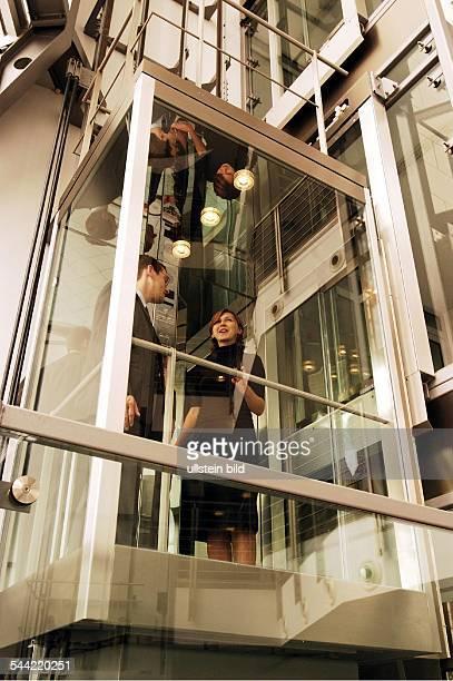 Junge Frau im Gespräch mit ihrem Kollegen im Fahrstuhl
