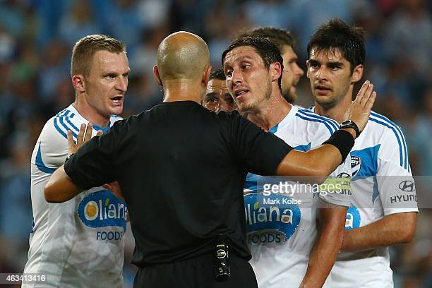 Besart Berisha and Mark Milligan of Melbourne Victory argue with referee Strebre Dilovski after he awarded a penalty during the round 17 ALeague...