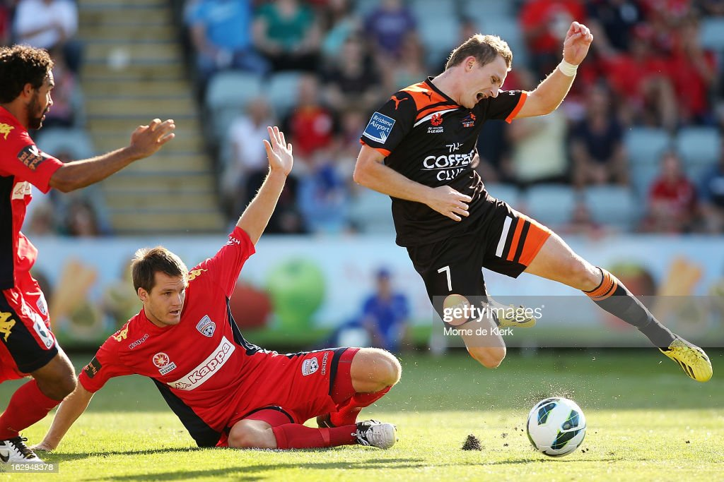 Besart Berisha (R) of Brisbane is brought down by Nigel Boogaard of Adelaide during the round 23 A-League match between Adelaide United and the Brisbane Roar at Hindmarsh Stadium on March 2, 2013 in Adelaide, Australia.