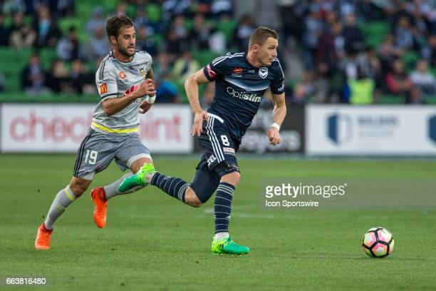 Besart Berisha of Melbourne Victory runs with the ball in front of Thomas Doyle during the round 25 match of the Hyundai ALeague between Wellington...