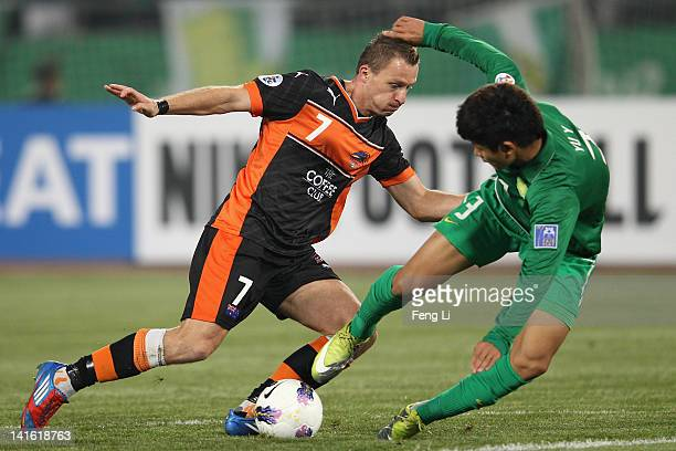 Besart Berisha of the Roar completes the ball with Yu Yang of Guoan during the AFC Champions League Group F match between China's Beijing Guoan and...