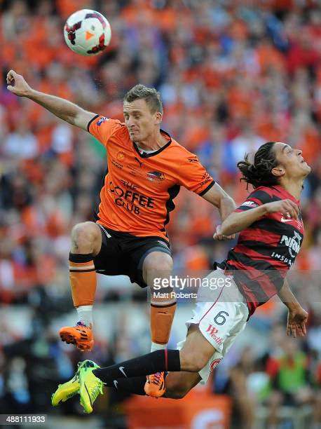 Besart Berisha of the Roar heads the ball towards the goal over Jerome Polenz of the Wanderers during the 2014 ALeague Grand Final match between the...