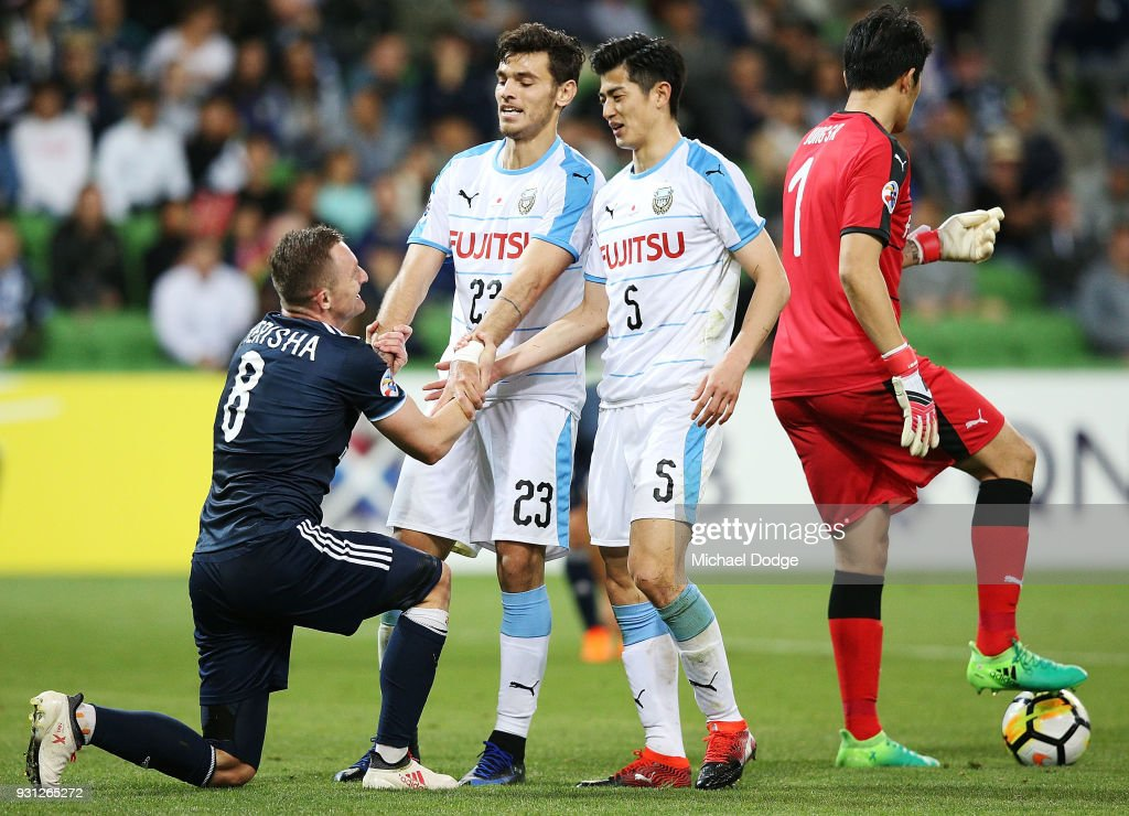Besart Berisha of the Victory is picked up by Eduardo and Shogo Taniguchi of Kawasaki Frontale (R) in the square during the AFC Asian Champions League match between the Melbourne Victory and Kawasaki Frontale at AAMI Park on March 13, 2018 in Melbourne, Australia.
