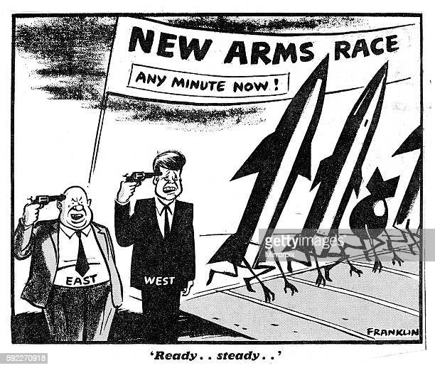 Beside the track are Nikita Khrushchev and President Kennedy with guns aginst their heads Cartoon refers to the Arms Race between the USSR and the...