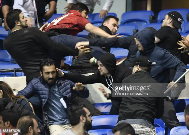 TOPSHOT Besiktas' and Lyon's supporters fight before the UEFA Europa League first leg quarter final football match between Lyon and Besiktas on April...