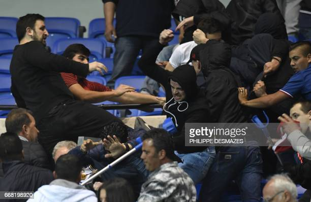 Besiktas' and Lyon's supporters fight in the tribune before the UEFA Europa League first leg quarter final football match between Lyon and Besiktas...
