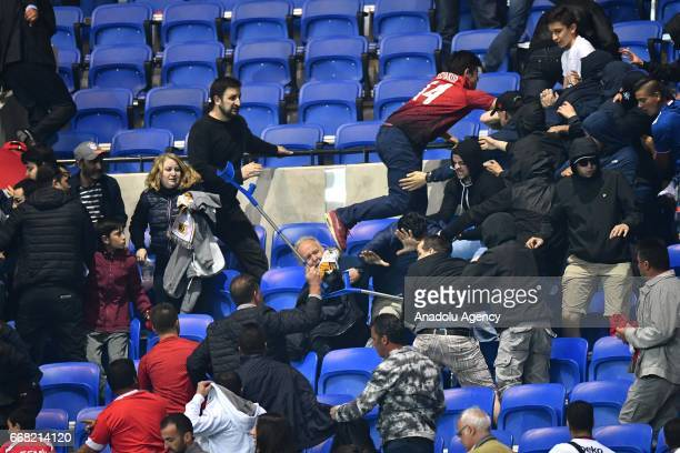 Besiktas' and Lyon's supporters fight in the tribune before the UEFA Europa League first leg quarter final football match between Olympique Lyonnais...