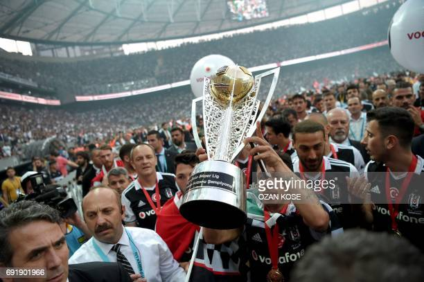 Besiktas' Brazilian defender Adriano holds the trophy as he and teammates celebrate their 20162017 Turkish league champion title after the Turkish...