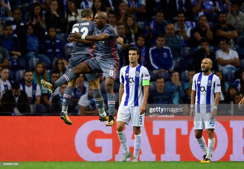TOPSHOT - Besiktas' Dutch midfielder Ryan Babel (2ndL) celebrates with teammate forward Cenk Tosun after scoring during the UEFA Champions League football match FC Porto vs Beskitas JK at the Dragao stadium in Porto on September 13, 2017. /