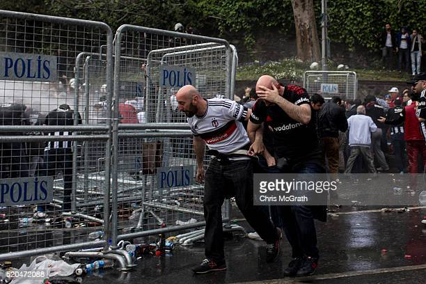 Besiktas fans cover their faces after police used tear gas to disperse fans trying to enter the stadium ahead of the opening match of the new...