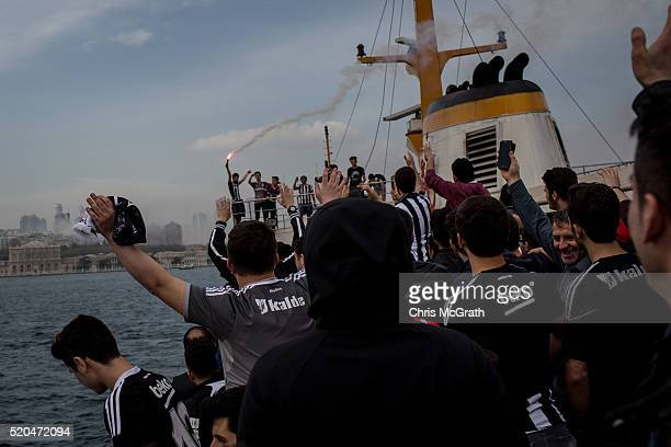 Besiktas fans light flares and cheer as they approach the stadium on a ferry ahead of the opening match of the new Vodafone Arena between Besiktas...